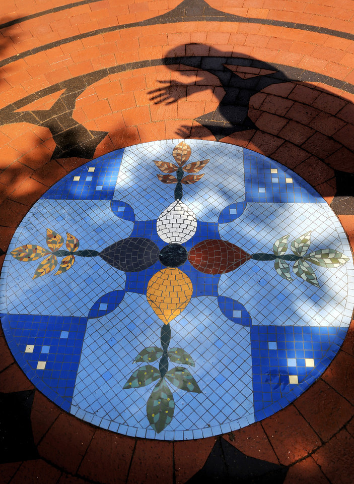 Photo -  The Rev. Susan Joplin, shown in shadow, discusses the symbolism included in the center medallion of the new HealingPath Labyrinth at the YWCA Passageways Shelter. Photo by Jim Beckel, The Oklahoman   Jim Beckel