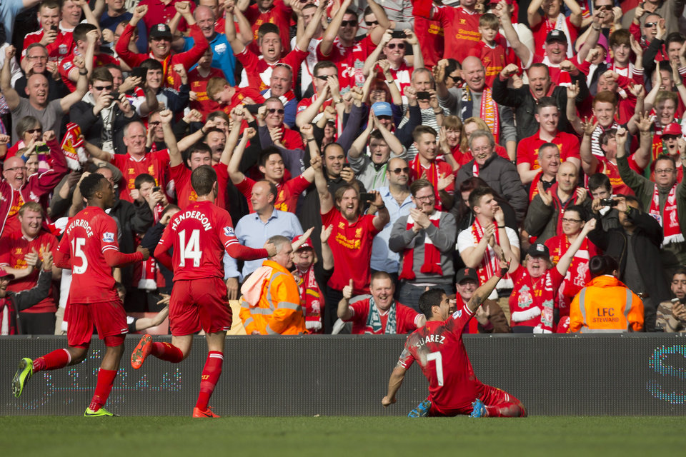 Photo - Liverpool's Luis Suarez , right, celebrates after scoring against Tottenham during their English Premier League soccer match at Anfield Stadium, Liverpool, England, Sunday March 30, 2014. (AP Photo/Jon Super)