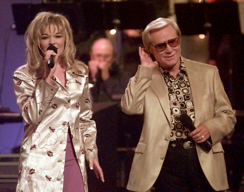 Photo - FILE - In this June 16, 1997 file photo, Country music veteran George Jones bends an ear toward 14-year-old newcomer LeAnn Rimes during the opening segment of the TNN-Music City News Country Awards show in Nashville, Tenn.,  Jones, the peerless, hard-living country singer who recorded dozens of hits about good times and regrets and peaked with the heartbreaking classic