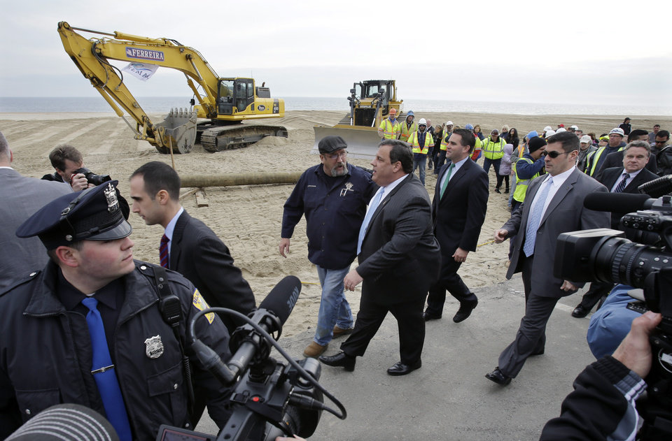 Photo - New Jersey Gov. Chris Christie, center right, walks with Belmar Mayor Matt Doherty, center second right, and others  Wednesday, Jan. 9, 2013, in Belmar, N.J., as officials kick off the construction on a 1.3-mile boardwalk to replace the walkway destroyed by Superstorm Sandy in October. The goal is to have it done by May. (AP Photo/Mel Evans)