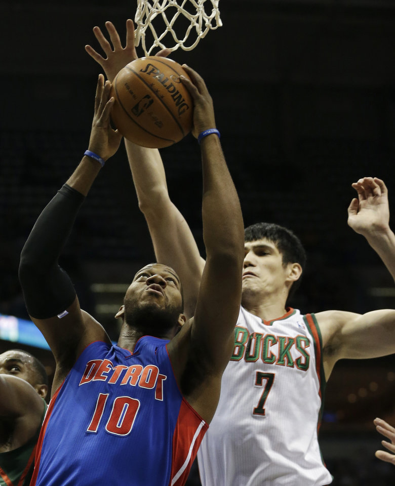 Photo - Detroit Pistons center Greg Monroe tries to score against Milwaukee Bucks forward Ersan Ilyasova, right, during the first half of an NBA basketball game Friday, Jan. 11, 2013, in Milwaukee. (AP Photo/Morry Gash)