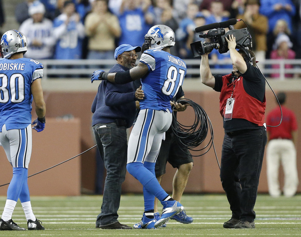 Detroit Lions wide receiver Calvin Johnson (81) hugs his father in the fourth quarter of an NFL football game against the Atlanta Falcons, after breaking Jerry Rice's single-season record for receiving yards, in Detroit on Saturday, Dec. 22, 2012. (AP Photo/Rick Osentoski)