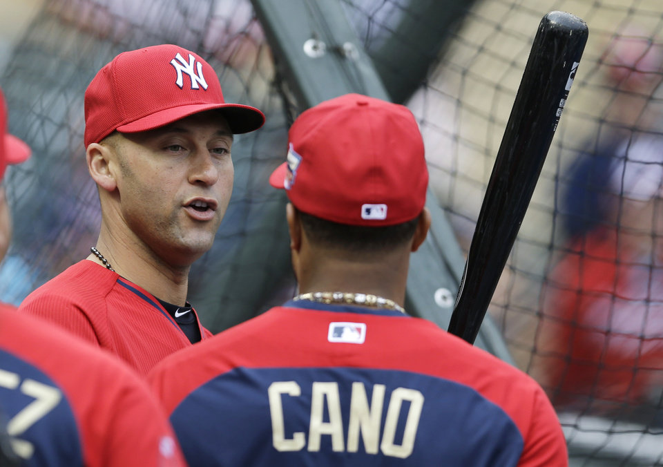 Photo - American League short stop Derek Jeter, of the New York Yankees, left, talks with teammate second baseman Robinson Cano, of the Seattle Mariners, during batting practice for the MLB All-Star baseball game, Monday, July 14, 2014, in Minneapolis. (AP Photo/Jeff Roberson)