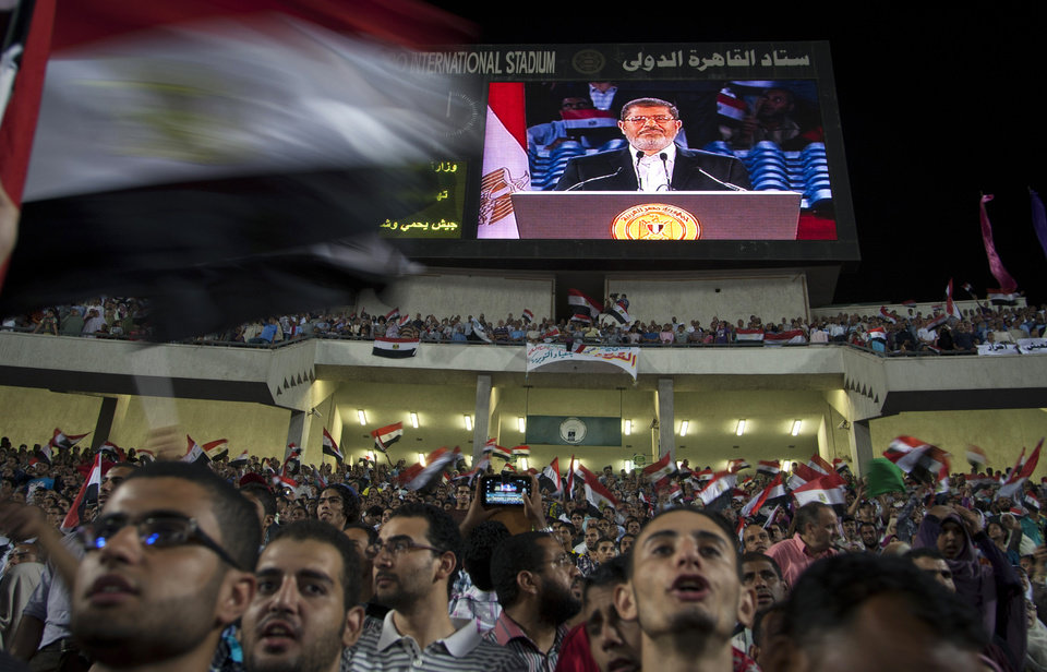 Egyptian President Mohammed Morsi is seen on a large screen as he speaks to a packed stadium on the 6th of October national holiday marking the 1973 war with Israel, Cairo, Egypt, Saturday, Oct. 6, 2012.(AP Photo/Khalil Hamra)