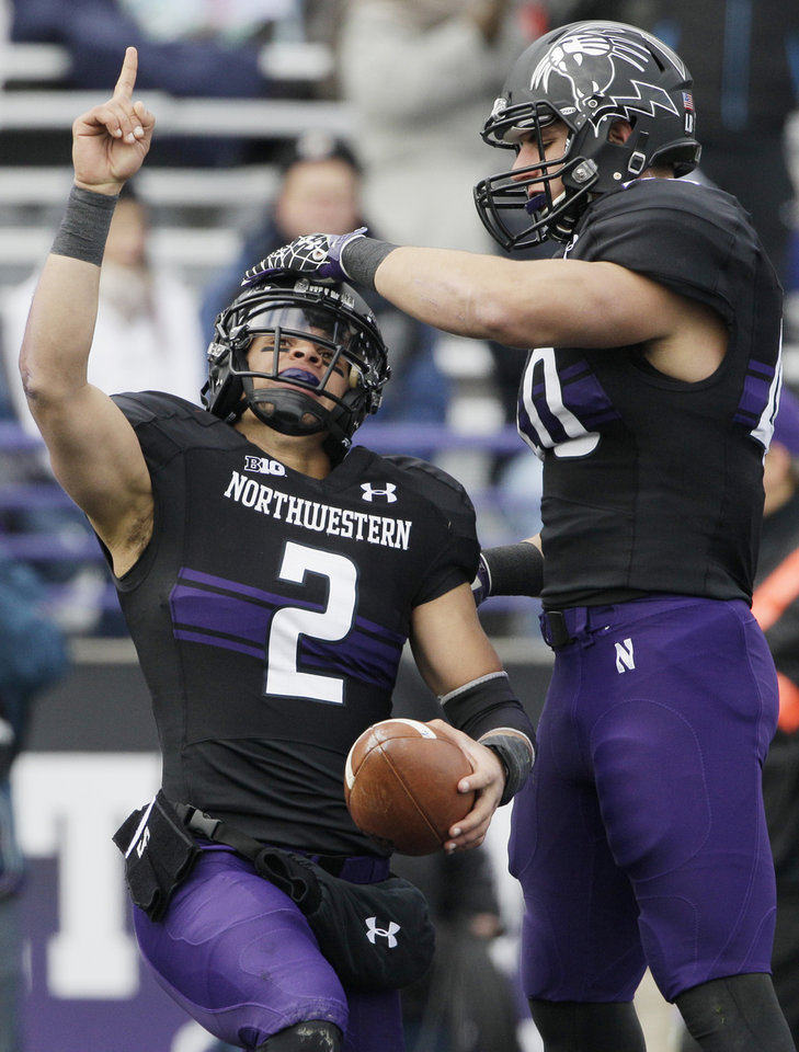 Photo -   Northwestern quarterback Kain Colter (2) points as he celebrates with slotback Dan Vitale (40) after scoring a touchdown during the first half of an NCAA college football game against Illinois in Evanston, Ill., Saturday, Nov. 24, 2012. (AP Photo/Nam Y. Huh)