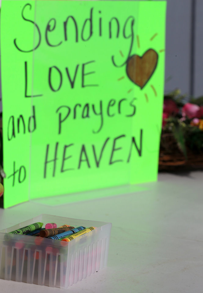 Photo - Crayons sit on a table outside of a barbershop a day after a gunman opened fire at Sandy Hook Elementary School, Saturday, Dec. 15, 2012, in the Sandy Hook village of Newtown, Conn. The massacre of 26 children and adults at Sandy Hook Elementary school elicited horror and soul-searching around the world even as it raised more basic questions about why the gunman, 20-year-old Adam Lanza, would have been driven to such a crime and how he chose his victims.  (AP Photo/Julio Cortez)