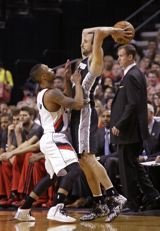 Photo - Portland Trail Blazers' Damian Lillard, left, guards San Antonio Spurs' Manu Ginobili in the first quarter during Game 4 of the Western Conference semifinal NBA basketball playoff series Monday, May 12, 2014, in Portland, Ore. (AP Photo/Rick Bowmer)