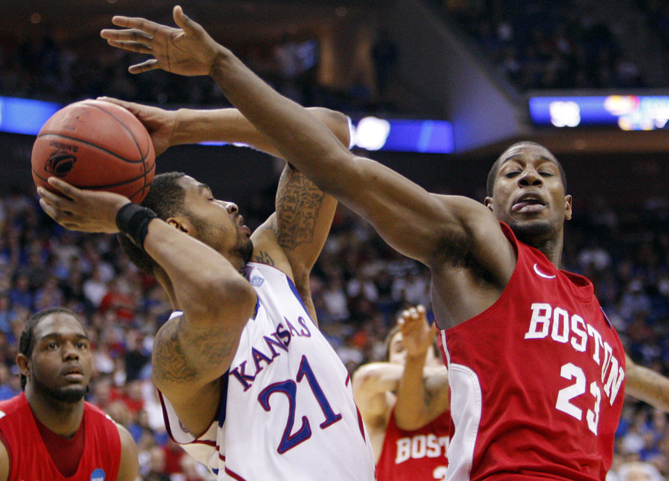 Photo - Boston's John Holland (23), right, tries to knock the ball away from Markieff Morris (21) of Kansas in the second half during the NCAA men's basketball tournament second round game between Boston and Kansas at the BOK Center in Tulsa, Okla., Friday, March 18, 2011. Kansas won, 72-53. Photo by Nate Billings, The Oklahoman