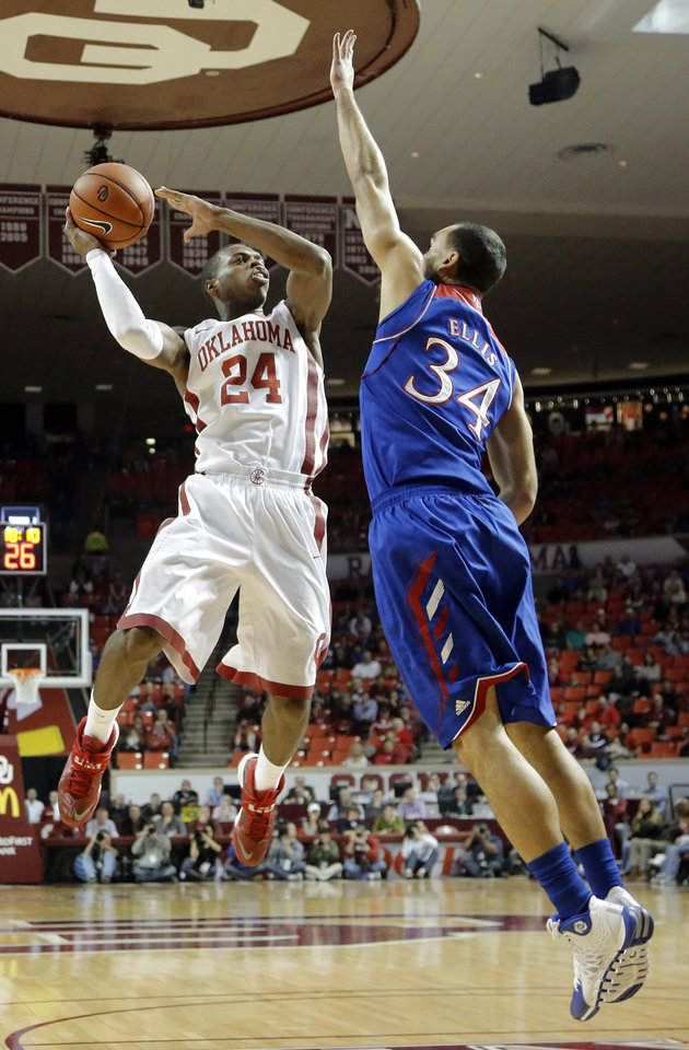 Photo - Oklahoma's Buddy Hield (24) drives against Kansas' Perry Ellis (34) during the NCAA college basketball game between the University of Oklahoma Sooners (OU) and the University of Kansas (KU) Jayhawks at Lloyd Nobel Center in Norman,  Okla. on Wednesday, Jan. 8, 2014.   .Photo by Chris Landsberger, The Oklahoman