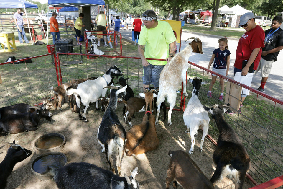 Photo - Children and parents enjoy a petting zoo during Bethany's Fourth of July events at Eldon Lyon Park in Bethany, OK, Friday, July 4, 2014,  Photo by Paul Hellstern, The Oklahoman