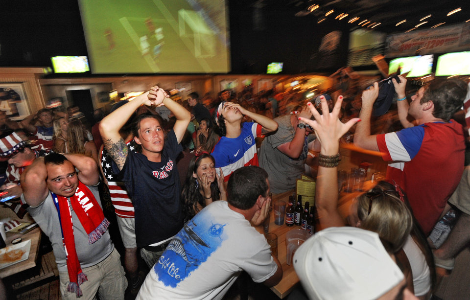 Photo - Craig Campbell, left, and Josh Trevino, second from left, react  as the United States misses a chance to score in a World Cup soccer match between the U.S. and Belgium, Tuesday, July 1, 2014, in Jacksonville Beach, Fla. (AP Photo/The Florida Times-Union, Bob Mack)