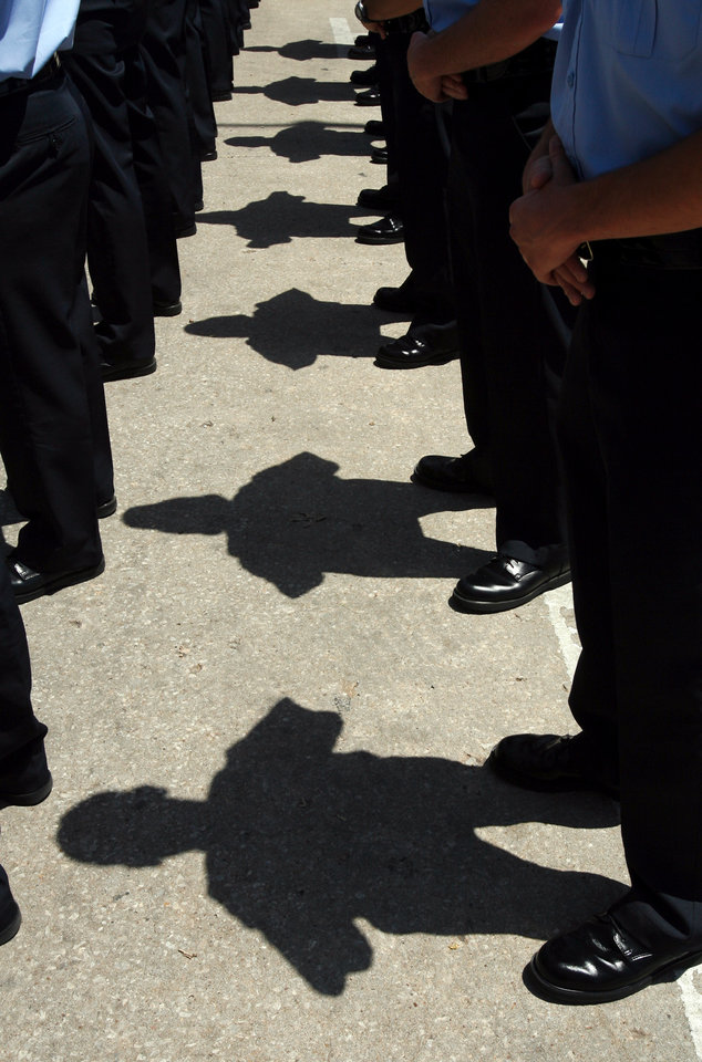 Photo - Officers bow during a ceremony honoring fallen officers in front of Oklahoma City Police Headquarters in Oklahoma City, Oklahoma on Friday, May 9, 2008.   BY STEVE SISNEY, THE OKLAHOMAN