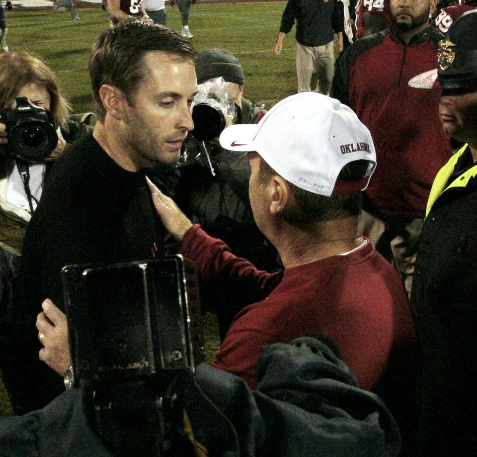 Tech head coach Kliff Klingbury and Sooner head coach Bob Stoops meet after a college football game where  the University of Oklahoma Sooners (OU) defeated the Texas Tech Red Raiders 38-30 at Gaylord Family-Oklahoma Memorial Stadium in Norman, Okla., on Saturday, Oct. 26, 2013. Photo by Steve Sisney, The Oklahoman