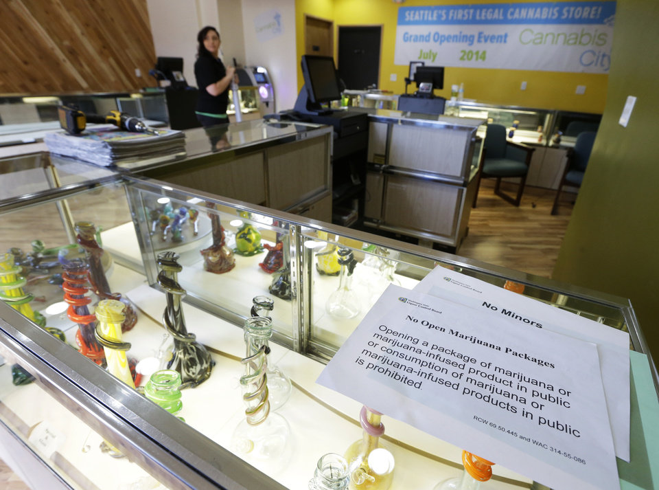 Photo - A sign noting the Washington state law that prohibits opening packages that contain marijuana or marijuana-infused products in public rests on a glass case displaying bongs for sale, Monday, July 7, 2014, at the recreational marijuana store Cannabis City in Seattle. The store will be the first and only store in Seattle to initially sell recreational marijuana when legal sales begin on Tuesday, July 8, 2014. (AP Photo/Ted S. Warren)