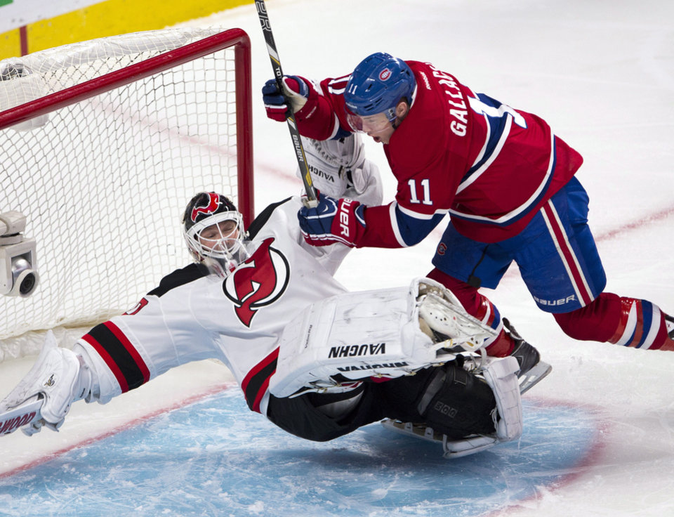 Photo - Montreal Canadiens right wing Brendan Gallagher (11) runs over New Jersey Devils goalie Martin Brodeur (30) during the first period of an NHL hockey game Tuesday, Jan. 14, 2014, in Montreal. (AP Photo/The Canadian Press, Ryan Remiorz)