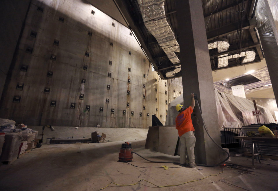 Photo - A contractor works on a column near the slurry wall, left, part of the World Trade Center's original foundation at the National September 11 Memorial and Museum, Friday, Sept. 6, 2013 in New York. Construction is racing ahead inside the museum as the 12th anniversary of the Sept. 11, 2001 attacks draws near. Several more large artifacts have been installed in the cavernous space below the World Trade Center memorial plaza. (AP Photo/Mary Altaffer)