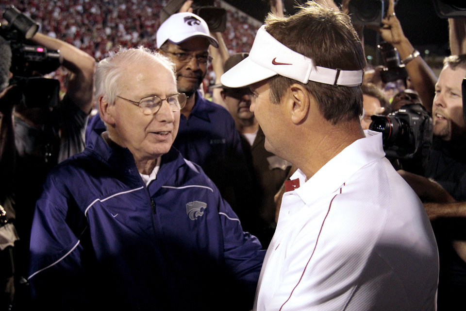 Photo - Kansas head coach Bill Self (left) and Sooner head coach Bob Stoops shake hands after the college football game where the University of Oklahoma Sooners (OU) lost 24-19 to the Kansas State University Wildcats (KSU) at Gaylord Family-Oklahoma Memorial Stadium, Saturday, September 22, 2012. Photo by Steve Sisney, The Oklahoman
