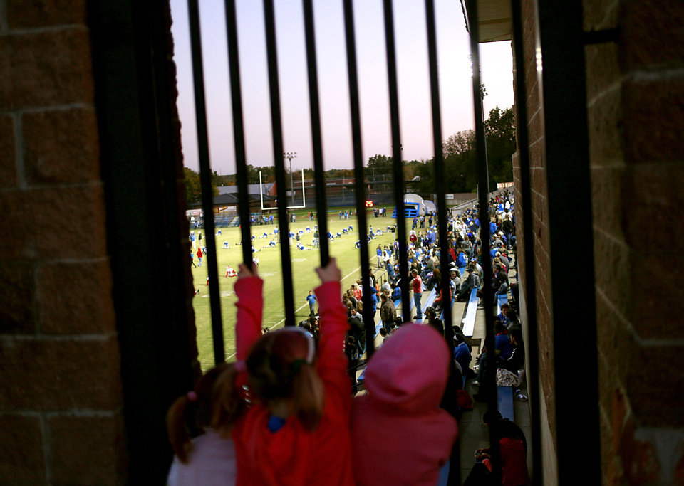 JELSMA STADIUM / THE ROCK / STADIUM / HIGH SCHOOL FOOTBALL: Dressed in pink for Breast Cancer awareness, young Bluejays fans hold onto a fence while they wait to get tickets to Guthrie's game against Western Heights in Guthrie on Friday, Oct. 28, 2011. Photo by John Clanton, The Oklahoman ORG XMIT: KOD