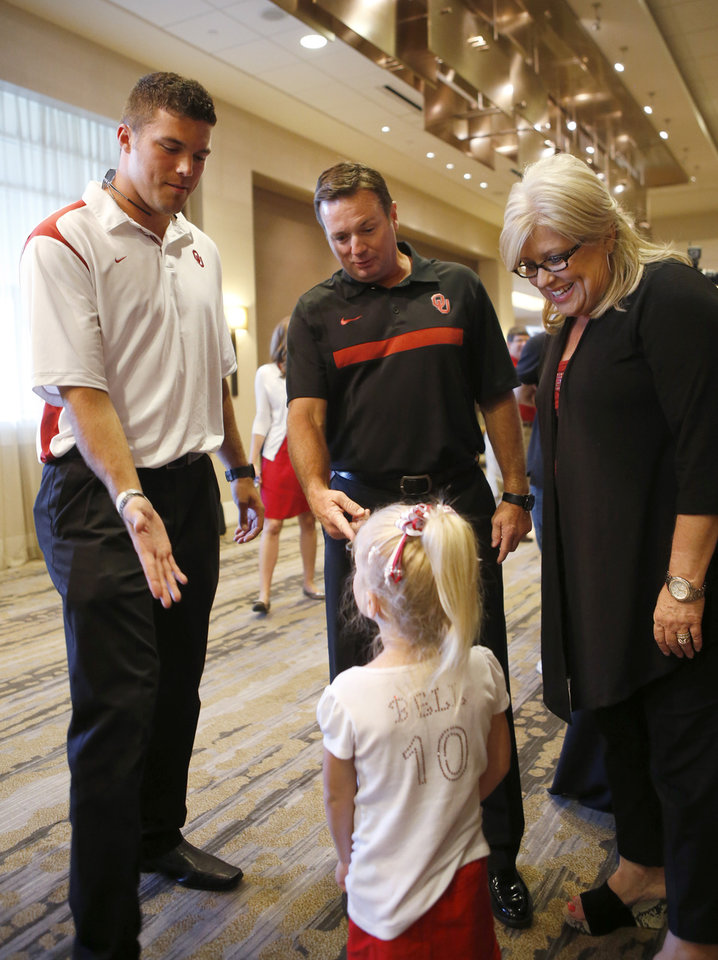 University of Oklahoma quarterback Blake Bell, introduces his 3-year-old relative Gentry Smith to OU head coach Bob Stoops during the Sooner Caravan stop at the Hyatt Wichita. Smith was wearing a sparkling homemade Bell jersey. Bell's mother Cherry Bell is at far right. (June 19, 2013) Photo by Jaime Green, The Wichita Eagle ORG XMIT: B73183861Z.1