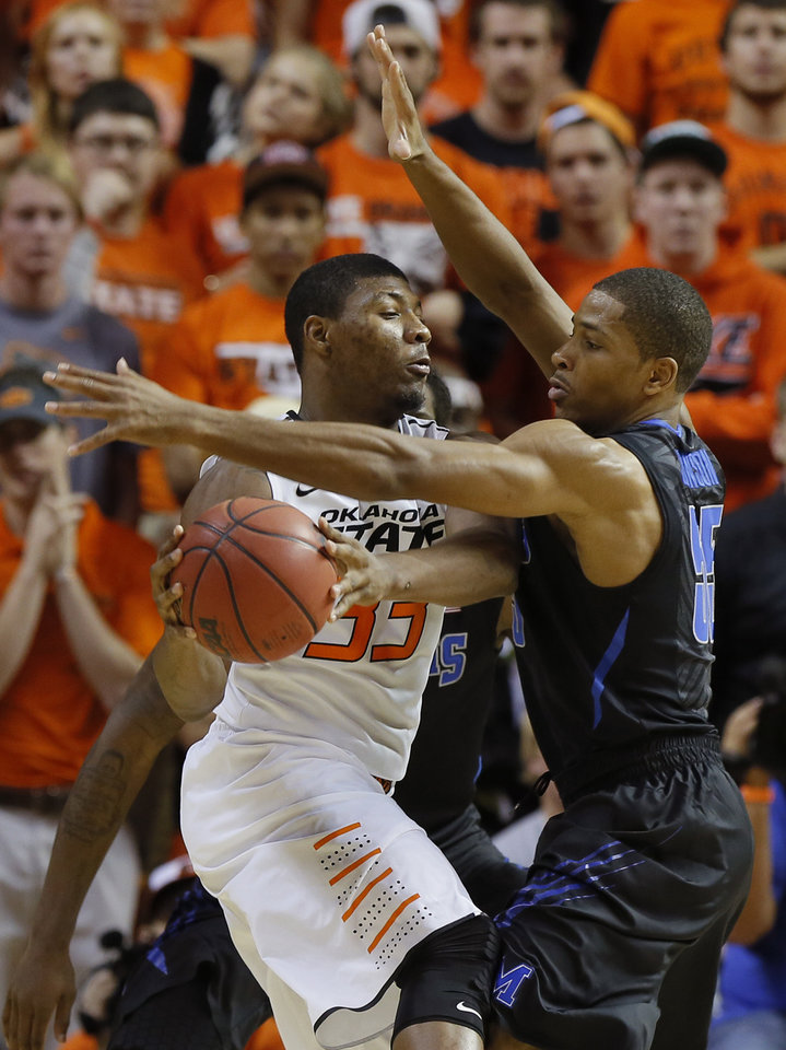 Photo - Oklahoma State's Marcus Smart (33) passes the ball around Memphis' Geron Johnson (55) during an NCAA college basketball game between Oklahoma State and Memphis at Gallagher-Iba Arena in Stillwater, Okla., Tuesday, Nov. 19, 2013. Photo by Bryan Terry, The Oklahoman