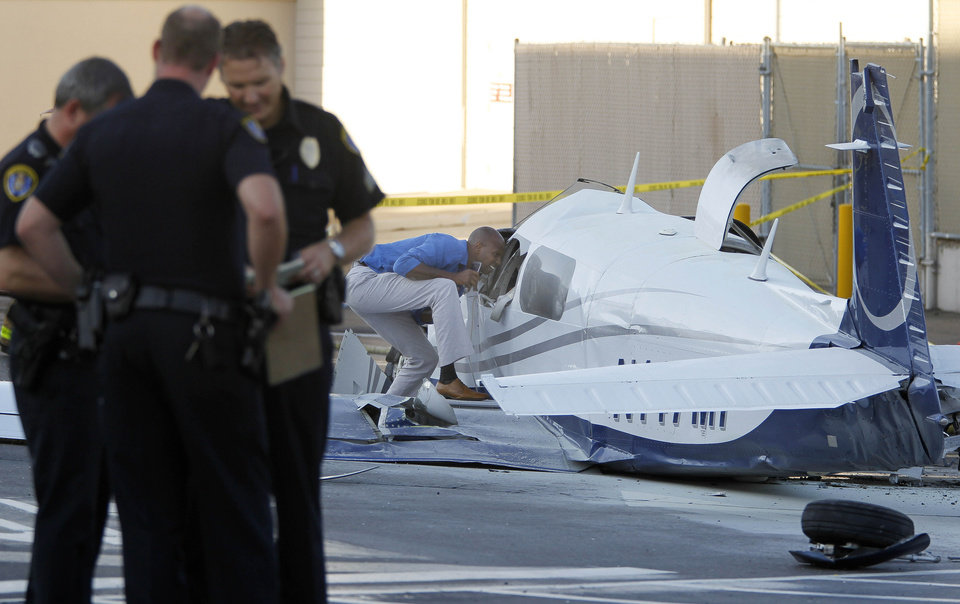 Photo - An aviation safety inspector, center, examine the wreckage of a small plane in the parking lot of shopping center Wednesday, July 30, 2014, in San Diego. Police said that one woman was killed and one hurt in the crash. (AP Photo/U-T San Diego, Hayne Palmour IV) NO SALES; MANDATORY CREDIT; TV OUT; MAGAZINES OUT; COMMERCIAL INTERNET OUT