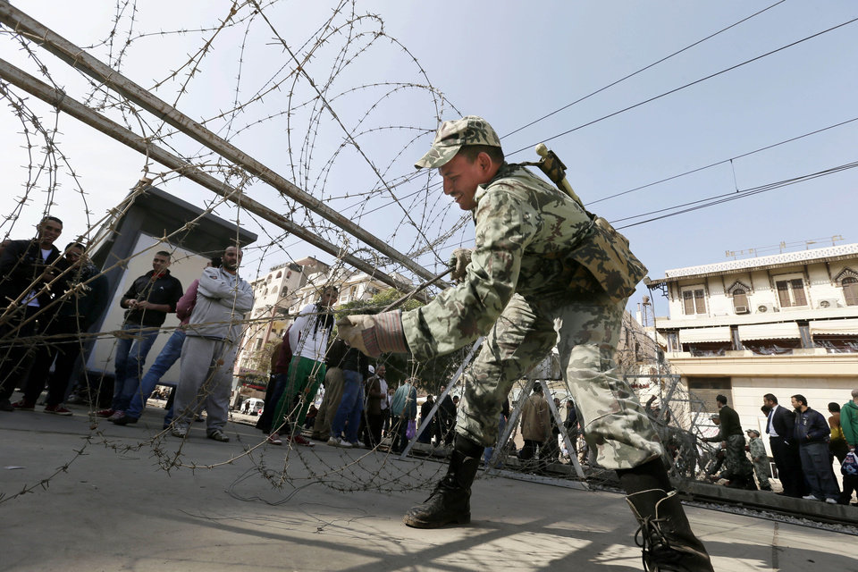Photo - An Egyptian Army soldier lays barbed wire near the presidential palace to secure the site of overnight clashes between supporters and opponents of President Mohammed Morsi in Cairo, Egypt, Thursday, Dec. 6, 2012. The Egyptian army has deployed tanks outside the presidential palace in Cairo following clashes between supporters and opponents of Mohammed Morsi that left several people dead and hundreds wounded. (AP Photo/Hassan Ammar)