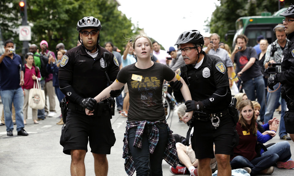 FILE -- In this Aug. 1, 2013 file photo, Seattle police officers take Caroline Durocher, center, into custody after Durocher sat in a downtown intersection during a protest by fast food workers and supporters in Seattle. Durocher works at a Subway sandwich shop. Washington already has the nation's highest state minimum wage at $9.19 an hour. Now, there's a push in Seattle, at least, to make it $15. That would mean fast food workers, retail clerks, baristas and other minimum wage workers would get what protesters demanded when they shut down a handful of city restaurants in May and others demonstrated nationwide in July. (AP Photo/Elaine Thompson, File)
