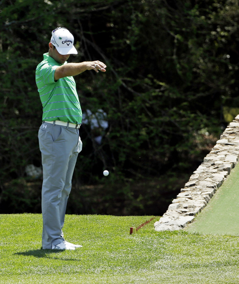 Photo - Gary Woodland takes a ball drop after his tee shot from the 12th hole landed in the water during the third round of the Masters golf tournament Saturday, April 12, 2014, in Augusta, Ga. (AP Photo/David J. Phillip)