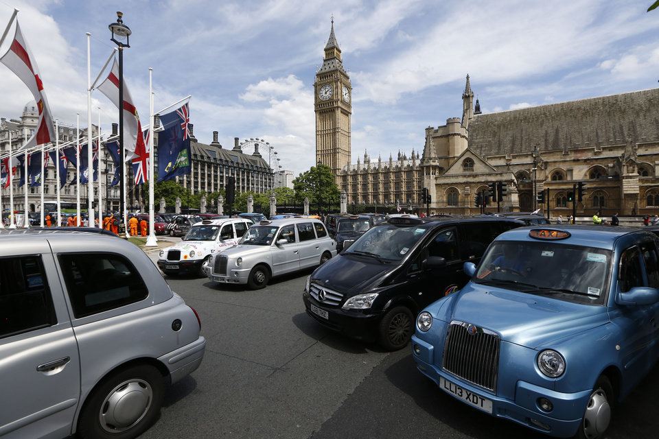 Photo - Taxi stand still at Parliament Square in central London as thousands of London black cabs blocking the streets to protest over new technology they say endangers passengers, in London, Wednesday, June 11, 2014.  The strike action by taxi drivers hit many European cities, Wednesday, sparked by fears about the growing upheaval in the travel and transport industry, largely due to digital technologies. Big Ben's clock tower back centre. (AP Photo/Sang Tan)