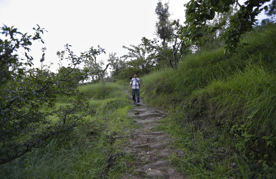 Photo -   In this Aug. 24, 2012 photo, Bhuwan Butholia, like many of his colleagues, walks through the hilly terrain on his way to and from the B2R center in Simayal, India. Before B2R arrived in Simayal, Butholia used to work in an auto parts factory 150 kilometers (90 miles) away, spending whatever he earned on food and rent. (AP Photo/Saurabh Das)