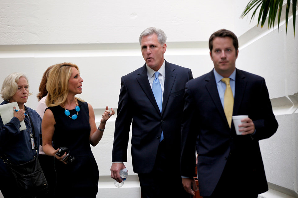 Photo - House Majority Whip Kevin McCarthy, R-Calif., center, walks to a Republican caucus at the U.S. Capitol in Washington, Saturday, Sept. 28, 2013. Lawmakers from both parties urged one another in a rare weekend session to give ground in their fight over preventing a federal shutdown, with the midnight Monday deadline fast approaching. But there was no sign of yielding Saturday in a down-to-the-wire struggle that tea party lawmakers are using to try derailing President Barack Obama's health care law.  (AP Photo/Molly Riley)