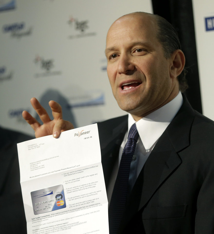 "Cantor Fitzgerald CEO Howard Lutnick displays a sample of the debit cards his company is distributing to Superstorm Sandy victims during a news conference in New York, Thursday, Jan. 10, 2013. The New York City financial services firm that lost the most workers in the Sept. 11 terror attacks announced that it will ""adopt"" 19 schools in communities hit hard by Superstorm Sandy and give a total of $10 million to families in those schools. (AP Photo/Seth Wenig)"