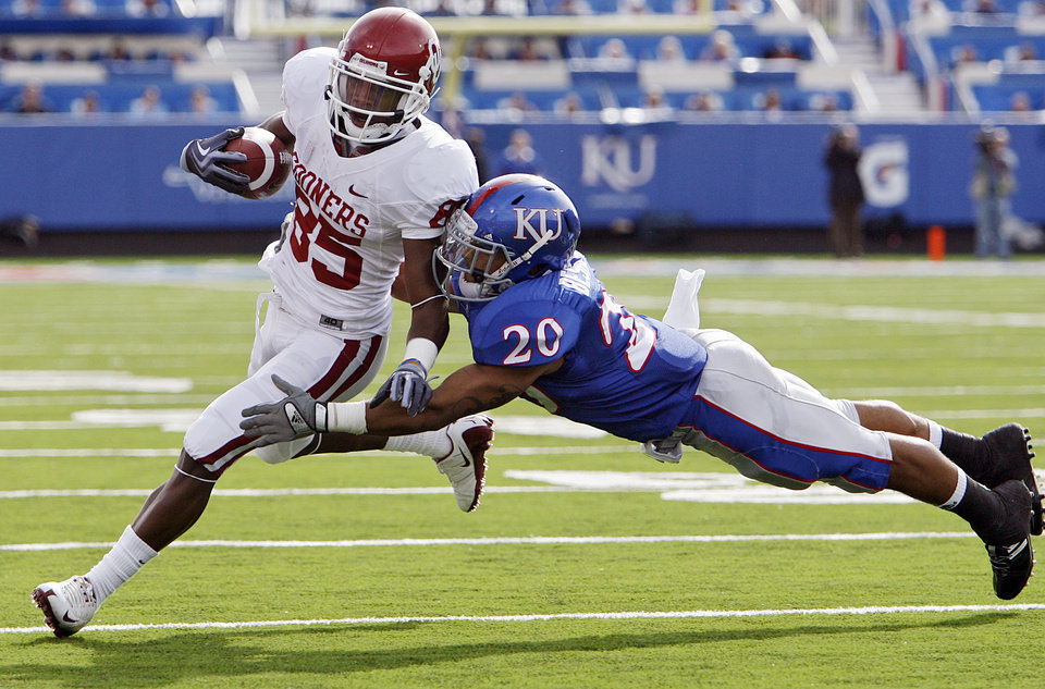 Photo - Oklahoma's Ryan Broyles (85) tries to get past Kansas' D.J. Beshears (20) during the first half of the college football game between the University of Oklahoma Sooners (OU) and the University of Kansas Jayhawks (KU) on Saturday, Oct. 24, 2009, in Lawrence, Kan. Photo by Chris Landsberger, The Oklahoman