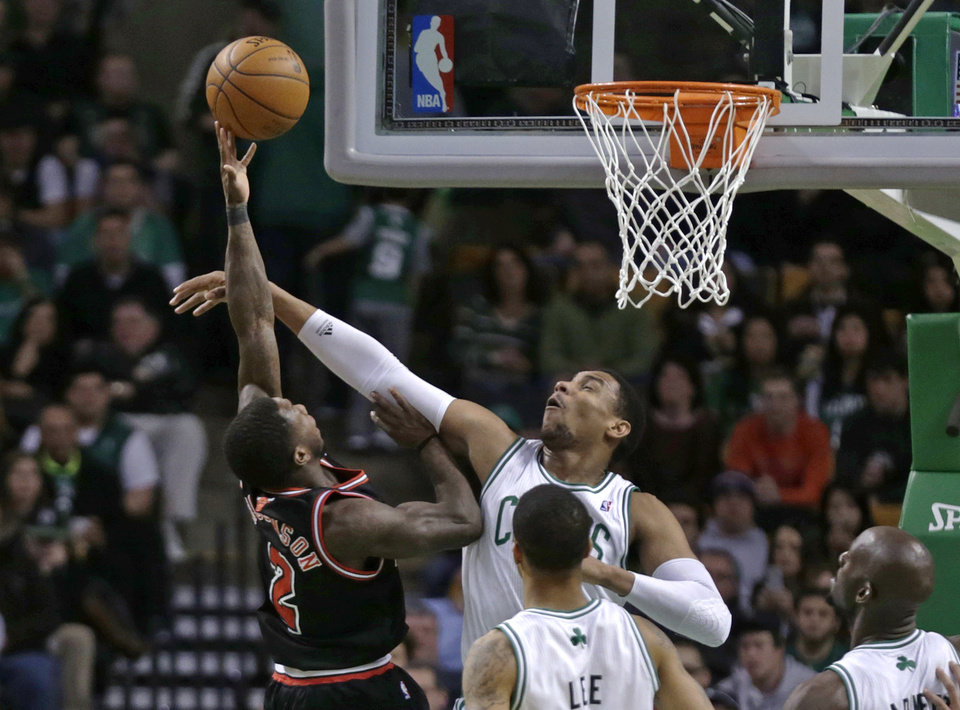 Photo - Boston Celtics forward Jared Sullinger blocks Chicago Bulls point guard Nate Robinson (2) on a drive to the basket during the first half of an NBA basketball game in Boston on Friday, Jan. 18, 2013. (AP Photo/Charles Krupa)