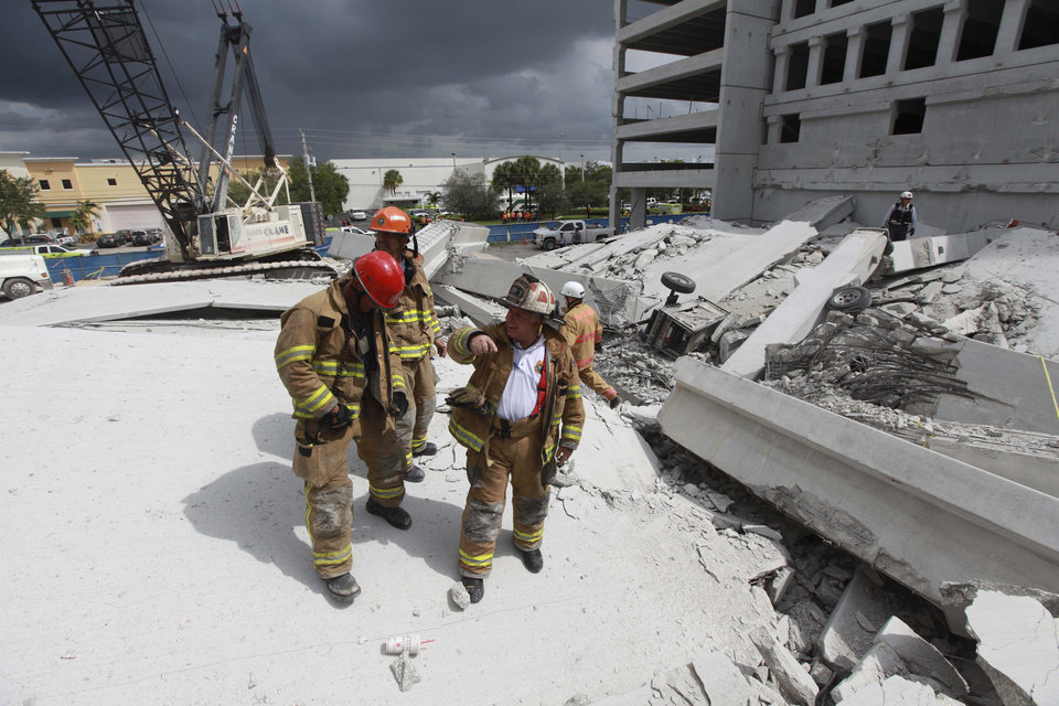Photo -   In a photo provided by Miami-Dade Fire Rescue, firefighters look over the rubble after a section of a parking garage under construction at a Miami-Dade College campus collapsed, Wednesday, Oct. 10, 2012 in Doral, Fla., killing one worker and trapping at least two others in the rubble, officials said. (AP Photo/Miami-Dade Fire Rescue)