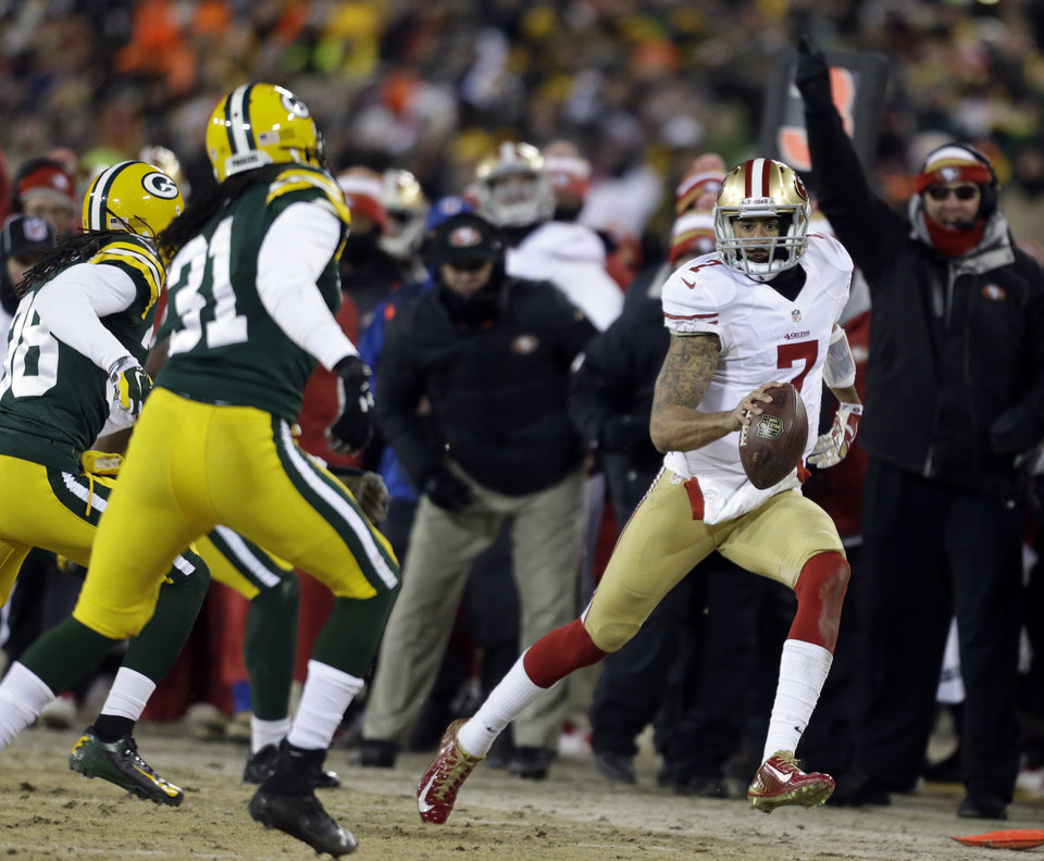 Photo - San Francisco 49ers quarterback Colin Kaepernick (7) scrambles for a first down against the Green Bay Packers defense during the second half of an NFL wild-card playoff football game, Sunday, Jan. 5, 2014, in Green Bay, Wis. The 49ers won 23-20. (AP Photo/Jeffrey Phelps)