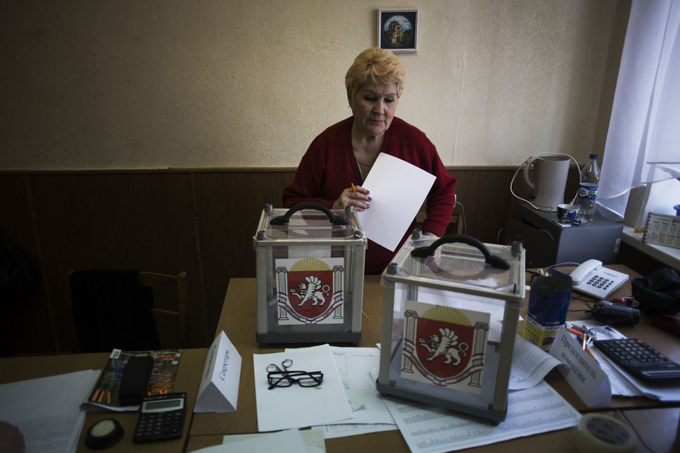 Photo - A Ukrainian woman, who is a member of the district electoral committee, makes final preparations as she stands next to ballot boxes for Sunday's referendum at a polling station in Simferopol, Ukraine, Saturday, March 15, 2014. Tensions are high in the Black Sea peninsula of Crimea, where a referendum is to be held Sunday on whether to split off from Ukraine and seek annexation by Russia. (AP Photo/Manu Brabo)