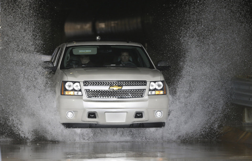 "In a Jan. 17, 2013 photo, a Chevrolet Suburban is driven through the flood test at the General Motors Milford Proving Grounds in Milford, Mich.  It's in this northwest Detroit suburb that GM has its testing facility, which, according to GM consumer affairs chief James Bell, exists for the purpose of beating ""the heck out of a vehicle before the customer can.� Founded in 1924, the 4,000-acre Milford Proving Grounds was the first dedicated automotive testing facility in the world, and remains one of the largest to this day. (AP Photo/Carlos Osorio)"