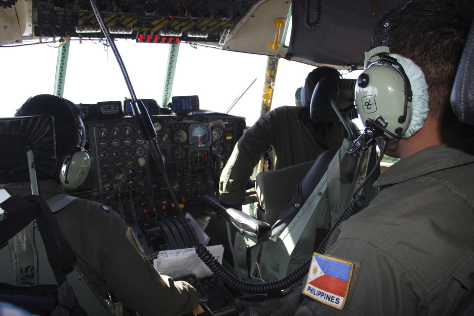 Photo - In this photo taken Tuesday, March 11, 2014, Philippine Air Force C-130 crew members continue their search and rescue mission over the South China Sea more than four days after a Malaysia Airlines jetliner went missing en route to Beijing. Authorities acknowledged Wednesday they didn't know which direction the plane carrying 239 passengers was heading when it disappeared, vastly complicating efforts to find it. Several dozen ships and aircraft from some 12 countries are continuing the search for the missing Boeing 777. (AP Photo/Philippine Air Force Western Command)