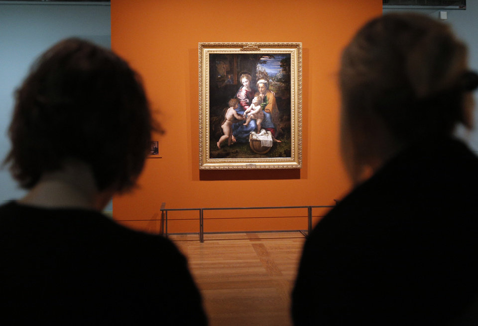 "Women watch ""Holy Family (La Perla) "", a painting by Raphael as part of the exhibition ""Late Raphael"" at the Louvre museum, in Paris, Tuesday, Oct. 9, 2012. This exhibition, organized by the Louvre from Oct. 11 to Jan.14, 2013 in partnership with the Prado Museum, brings together the works produced by Raphael in Rome during the last years of his life. (AP Photo/Christophe Ena"