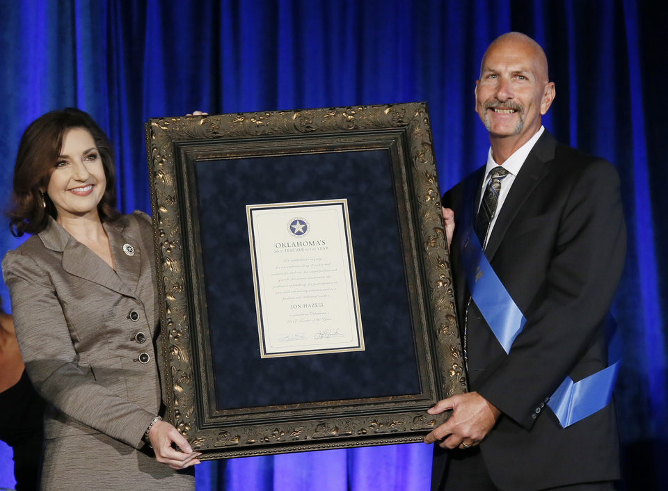 Photo - Jon Hazell, right, a science teacher at Durant High School, is pictured with Oklahoma State Schools Superintendent Joy Hofmeister, left, after being named Oklahoma's Teacher of the Year for 2017, during a ceremony in Oklahoma City, Tuesday, Aug. 30, 2016. Hazell was named Oklahoma Teacher of the Year after extensive interviews with 12 finalists by a 28-member panel. (AP Photo/Sue Ogrocki)