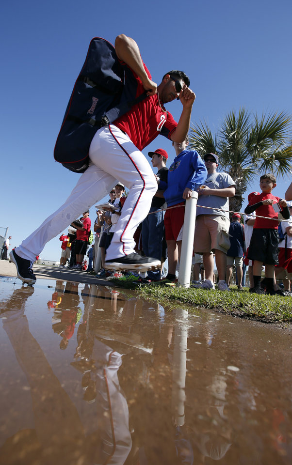 Photo - Washington Nationals starting pitcher Gio Gonzalez hops a puddle after signing autographs following a spring training baseball workout, Monday, Feb. 17, 2014, in Viera, Fla. (AP Photo/Alex Brandon)