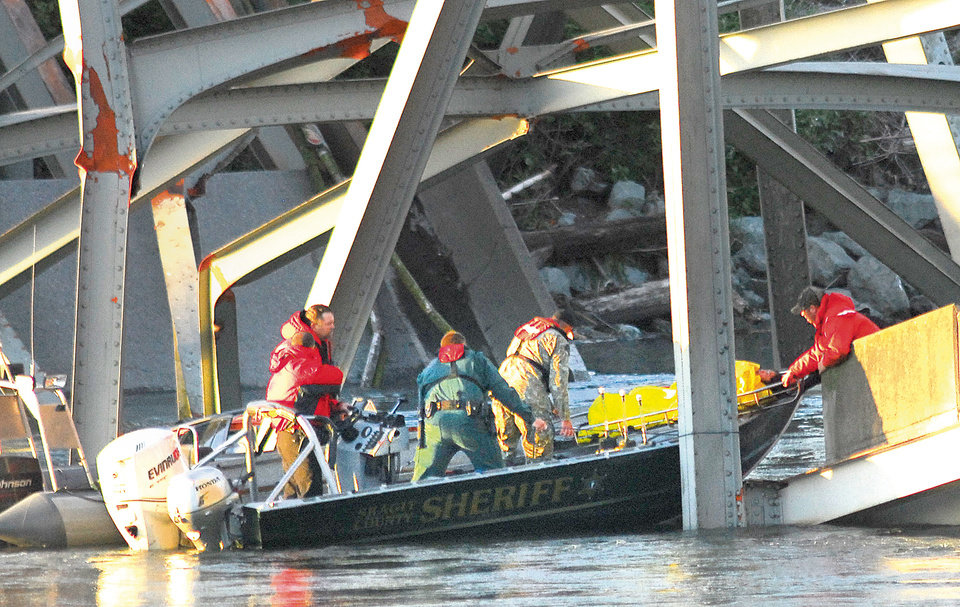 Photo - A person is removed from the wreckage of the collapsed Interstate-5 bridge in Mount Vernon, Wash. Thursday May 23, 2012. The Interstate 5 bridge over the Skagit river collapsed north of Seattle Thursday evening, dumping two vehicles into the water and sparking a rescue effort by boats and divers as three injured people were pulled from the chilly waterway. (AP Photo/Skagit Valley Herald, Frank Varga)