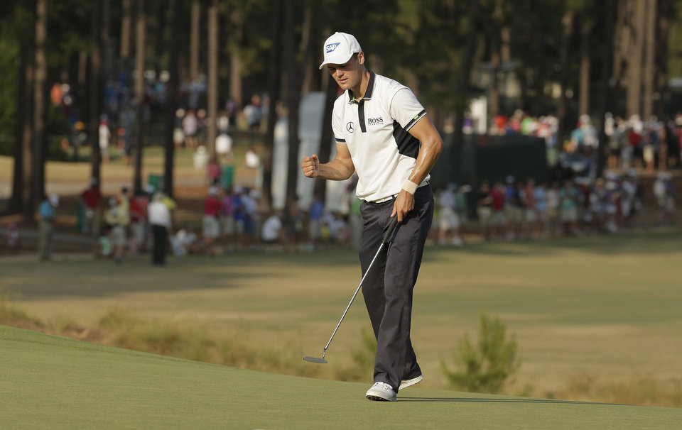 Photo - Martin Kaymer, of Germany, reacts to his putt on the 13th hole during the final round of the U.S. Open golf tournament in Pinehurst, N.C., Sunday, June 15, 2014. (AP Photo/Charlie Riedel)
