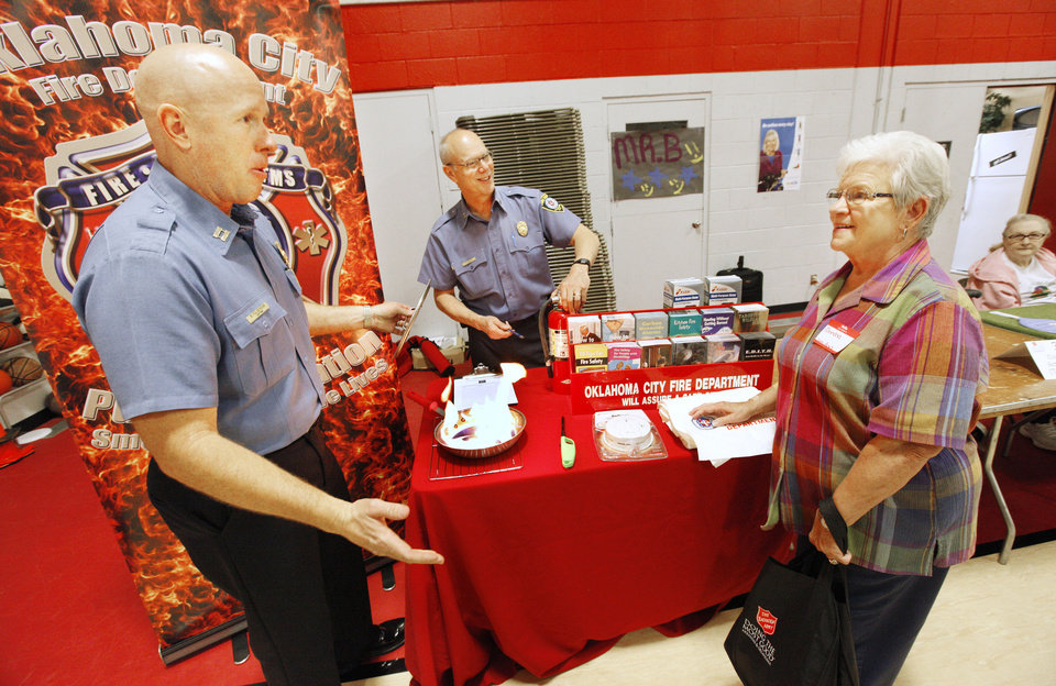 Photo - Capt. Benny Fulkerson and Capt. Mark Corvin, with the Oklahoma City Fire Department, speak with Sandra Rutherford, of Bethany, about how to put out grease fires in the kitchen during the Salvation Army Senior Living Fair. The fair was held during National Salvation Army Week. Photo by Paul B. Southerland, The Oklahoman  PAUL B. SOUTHERLAND - PAUL B. SOUTHERLAND