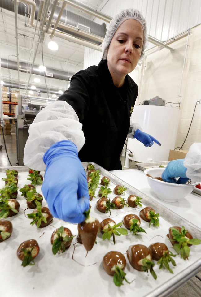 Photo -  Melissa Walker dips strawberries in chocolate at Bedre Fine Chocolate.    STEVE SISNEY -  THE OKLAHOMAN