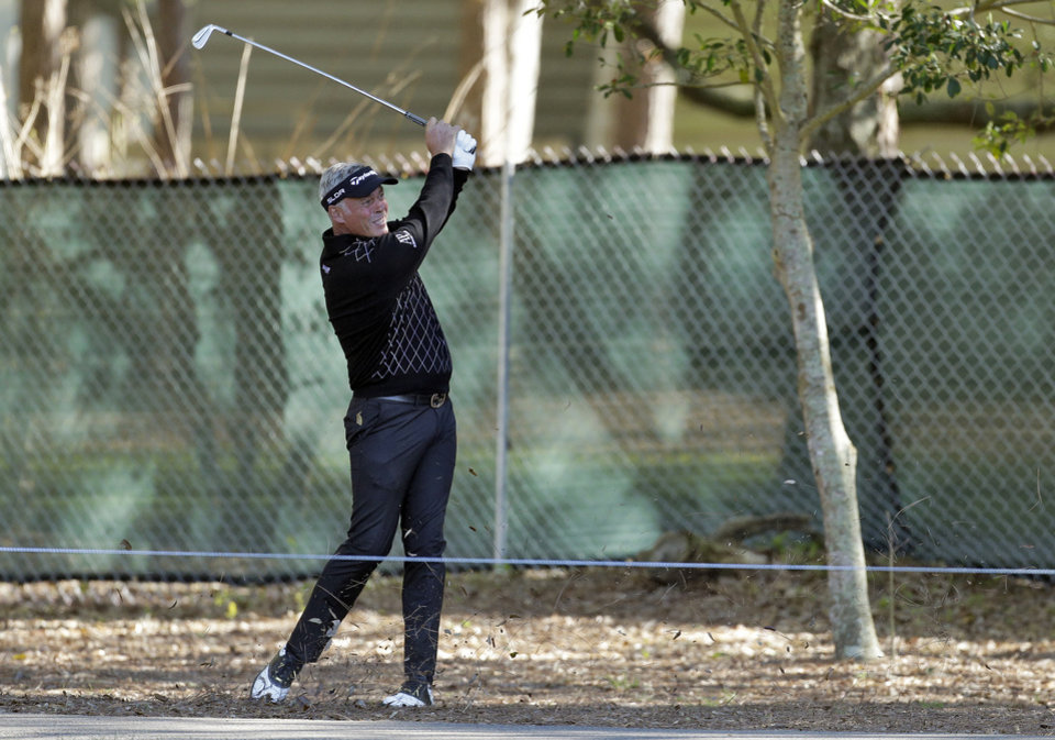Photo - Darren Clarke, of Northern Ireland, hits from off the fairway on the 12th hole during the first round of the Valspar Championship golf tournament at Innisbrook, Thursday, March 13, 2014, in Palm Harbor, Fla. (AP Photo/Chris O'Meara)