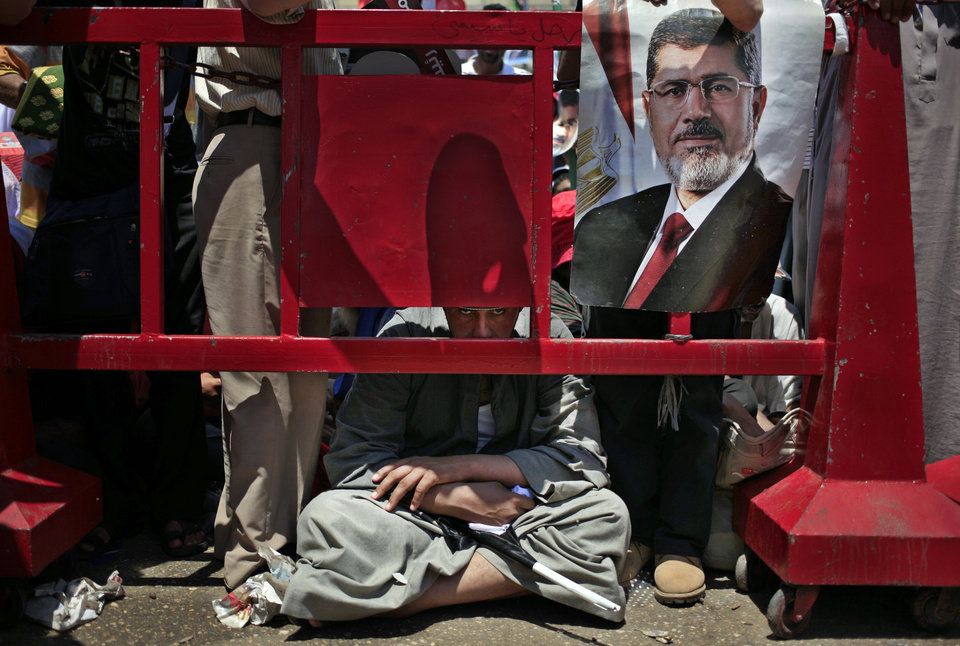 Photo - Supporters of Egypt's ousted President Mohammed Morsi attend the Friday prayer during a protest at Nasr City, where protesters have installed their camp and hold their daily rally, in Cairo, Egypt, Friday, July 26, 2013. Political allies of Egypt's military lined up behind its call for huge rallies Friday to show support for the country's top general, Abdel-Fattah el-Sissi, pushing toward a collision with Islamist opponents demanding the return of Mohammed Morsi, the nation's ousted president. (AP Photo/Khalil Hamra)
