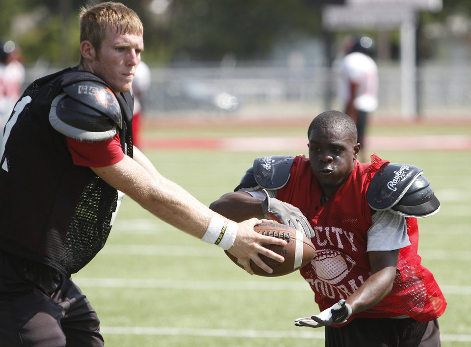 Photo - Jonathan McBride hands off the ball to Anthony Mason during high school football practice at Del City High School Friday, Aug. 12, 2011. Photo by Sarah Phipps, The Oklahoman