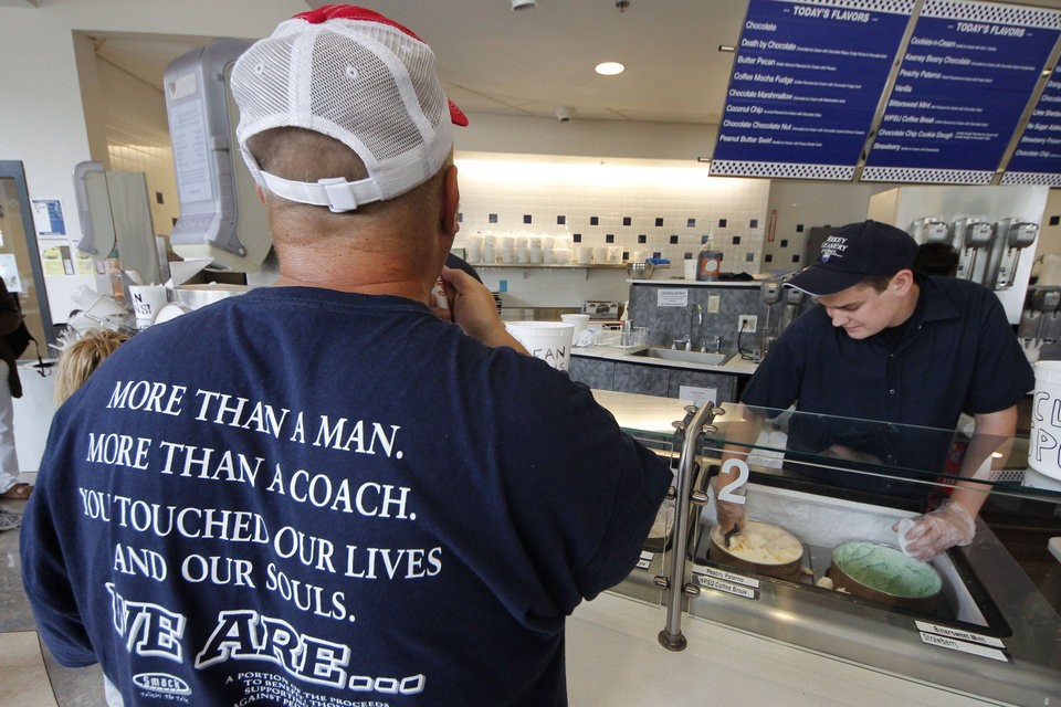 Photo -   A cup of Peachy Paterno ice cream is scooped for a customer wearing a shirt memorializing former Penn State head football coach Joe Paterno at the Berkey Penn State Creamery on the main campus of Penn State University in State College, Pa., Friday, July 13, 2012. (AP Photo/Gene J. Puskar)